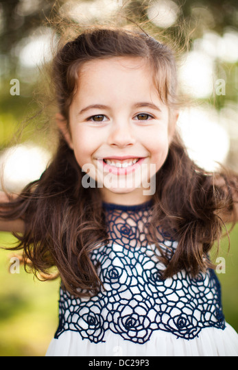 Portrait of girl with long brown hair looking at camera - Stock Image