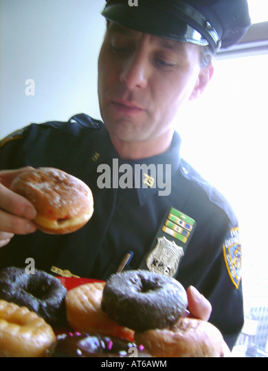 Portrait of a New York City Police Officer Near a Window He is About to Eat a Jelly Donut - Stock Image