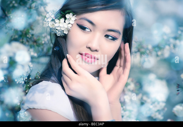 Young woman with cherry flowers. Soft blue tint. - Stock Image