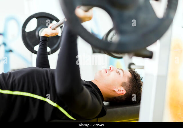 Closeup of young handsome male doing exercises on a bench press - Stock Image