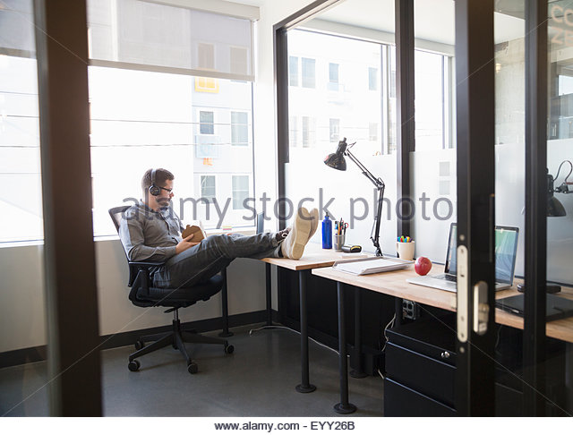 Caucasian businessman eating lunch at office desk - Stock Image