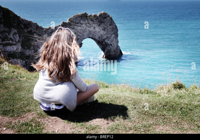girl sat by Durdle Door,Dorset,England,UK - Stock-Bilder