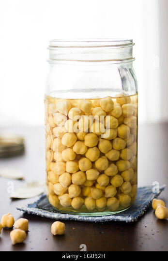 Chickpeas soaking in a jar - Stock Image