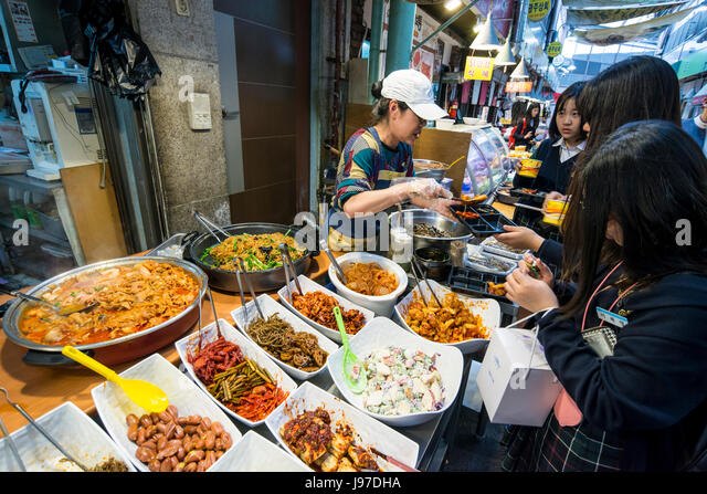 The vendor serving customers at a food stall in Tongin Market, Tongin dong, Seoul, South Korea - Stock Image