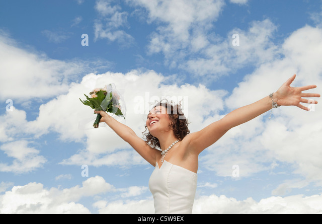 Germany, Bavaria, Smiling Bride with bouquet and arms outstreched , outdoors - Stock-Bilder