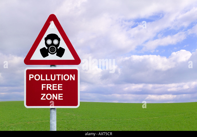 Image of a sign for a Pollution Free Zone against a green field and blue cloudy sky Environmental and Conservation - Stock Image