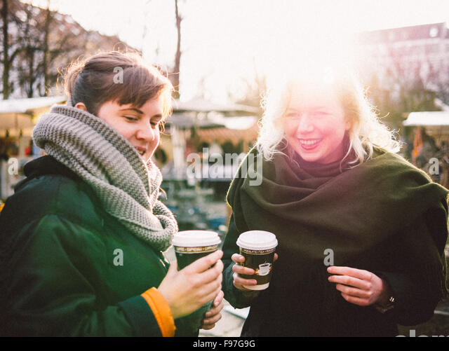 Happy Friends Holding Disposable Coffee Cup In Flea Market - Stock Image