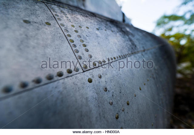 The rivot panels on the fuselage of a wrecked DC-3 in the forest after crashing during WWII. - Stock Image