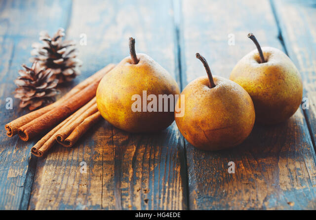 Organic pears with cinnamon sticks on a wooden table - Stock Image