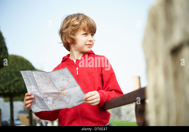 Young boy holding map in park, Province of Venice, Italy - Stock Image