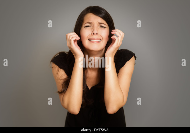 Distraught tearful young woman with her hands clasped in anguish standing with downcast eyes against a white studio - Stock Image