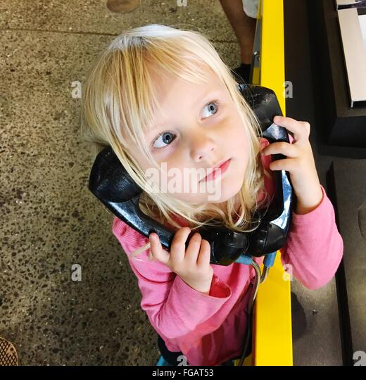 High Angle View Of Girl Holding Telephone Receivers On Booth - Stock Image