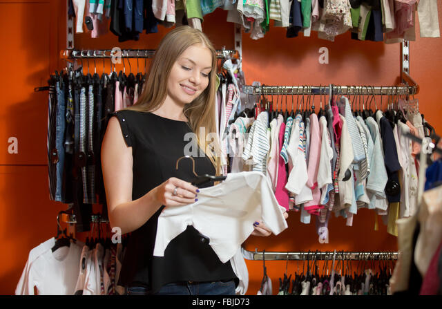 Portrait of smiling young beautiful woman shopping, standing in department store with baby clothes, choosing new - Stock Image