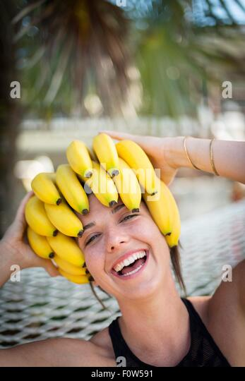 Portrait of young woman at beach with bananas on head, Islamorada, Florida, USA - Stock-Bilder