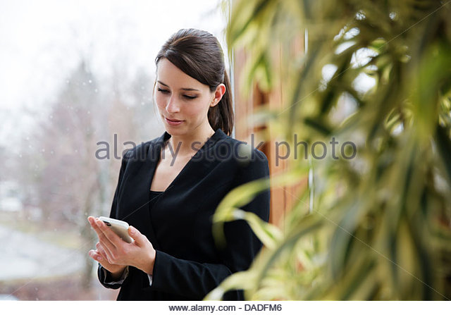 Woman looking at mobile phone - Stock Image