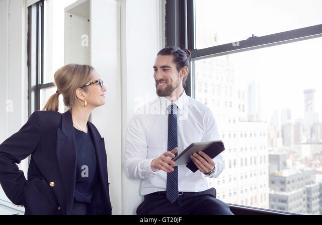 Smiling businessman talking to female colleague while holding digital tablet - Stock-Bilder
