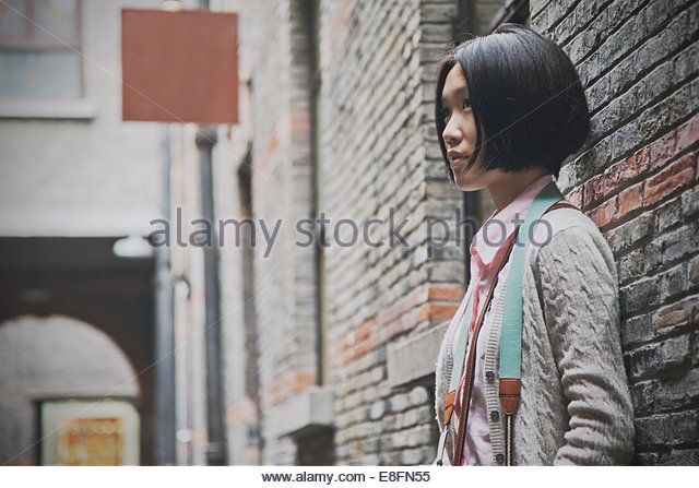 Young woman standing against wall, Huangpu District, Shanghai, China - Stock Image