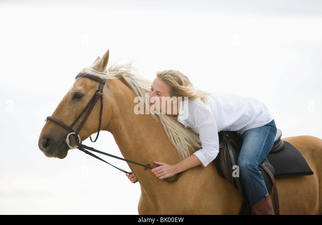 Girl with brown horse on the beach - Stock Image