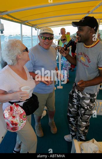 Sint Maarten Simpson Bay Lagoon Dutch Explorer Tour Boat Black male singer microphone senior couple dance - Stock Image