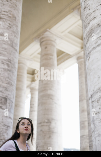 A woman looking up at the tall pillars and arches of a historic building in Rome. - Stock Image