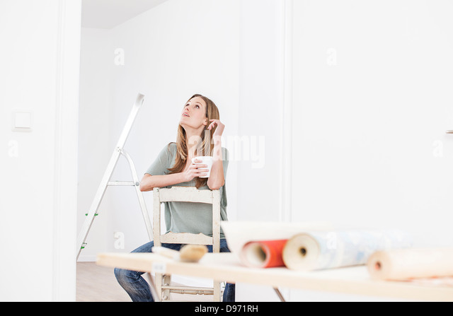 Woman sitting on chair with cup, wallpaper on table in foreground - Stock Image