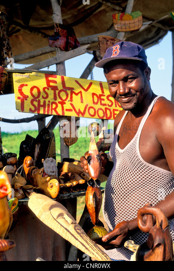 Negril Jamaica friendly vendor selling wood carvings at stand brightly colored in the Caribbean - Stock Image