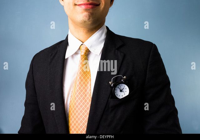 Young business man with a clock in his front pocket has time on his side - Stock Image