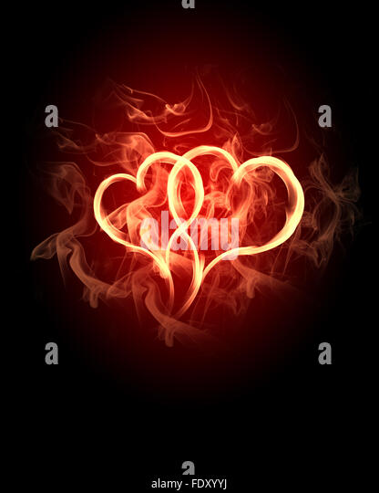 burning heart with flames against dark background - Stock Image