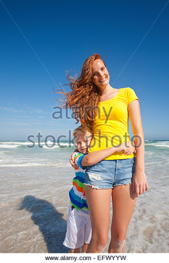 Portrait of son, with arms around smiling mother, on sunny beach - Stock Image