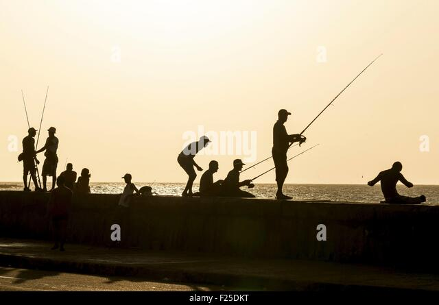 Cuba, Havana, Malecon, Habana Vieja district listed as World Heritage by UNESCO, fishermen at evening time - Stock Image