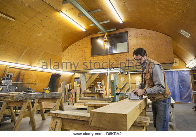 Woodworker using power plane on wooden beam - Stock Image