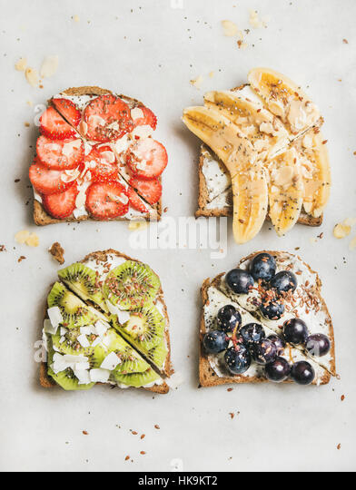 Healthy breakfast toasts. Wholegrain bread slices with cream cheese, various fruit, seeds and nuts. Top view, grey - Stock Image