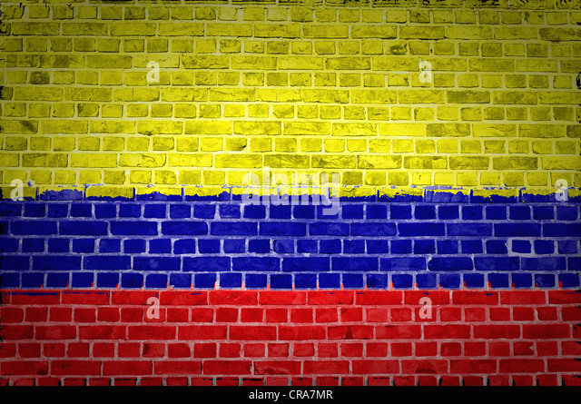 An image of the Colombia flag painted on a brick wall in an urban location - Stock Image
