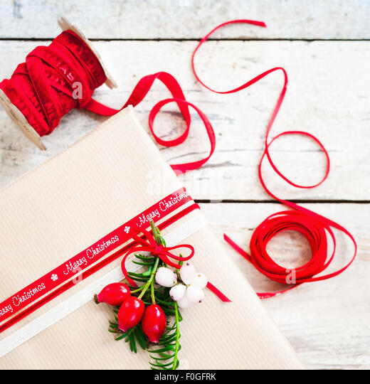 simple gift wrapped with brown paper and decorated with red ribbon and berries - Stock Image
