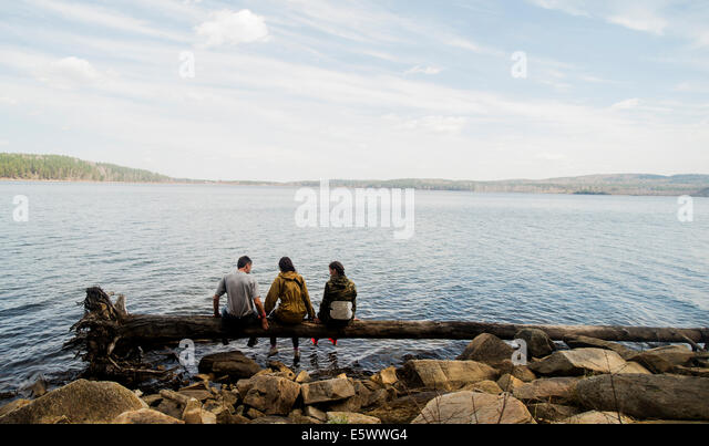 Three hiking friends sitting in a row on fallen tree at lakeside - Stock Image