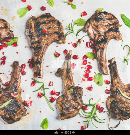 Slow food dinner with grilled lamb ribs and pomegranate, herbs - Stock Image