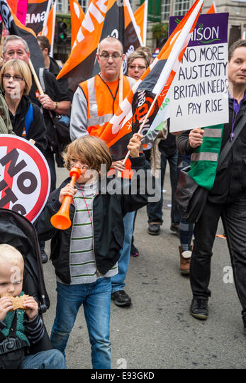 Cute boy with No Cuts on his face blowing a trumpet. Britain Needs a Pay Rise march, London, 18 October 2014, UK - Stock Image