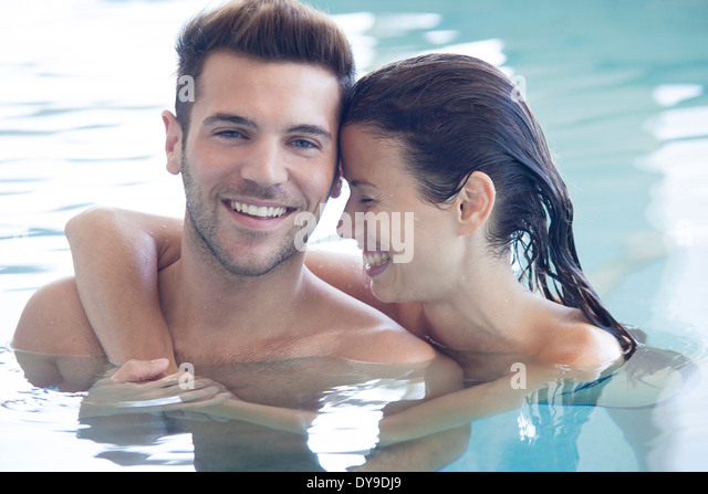 Young couple in pool together, portrait - Stock Image