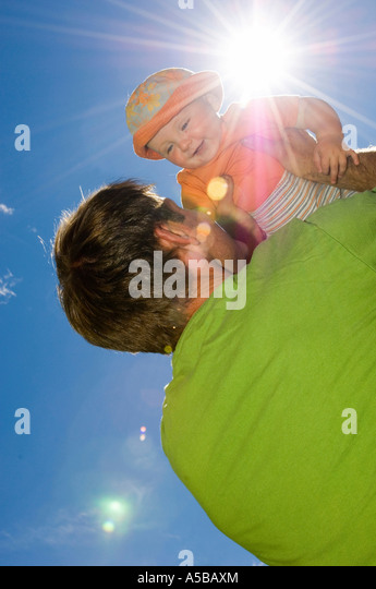 Dad lifting baby up to the sun. - Stock Image