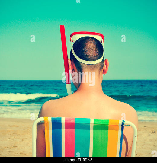 picture from the back of a man wearing a diving mask and a snorkel seated in a deckchair on the beach, with a retro - Stock-Bilder
