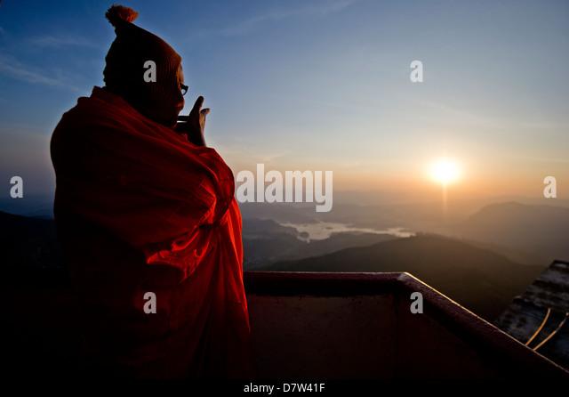 A monk looks out over a sunrise from the top of the sacred mountain Sri Pada (Adam's Peak), Sri Lanka - Stock Image