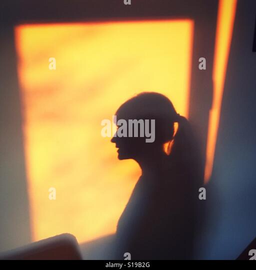 Afternoon silhouette of young woman - Stock Image