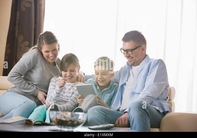 Cheerful family using tablet PC together in living room - Stock Image