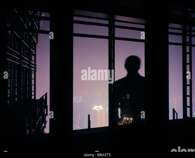 Silhouette of man in front of window looking at the skyline of Shanghai, China. - Stock Image