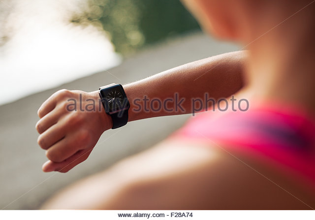 Close up image of young woman checking the time on smartwatch device after jog, outdoors. - Stock Image