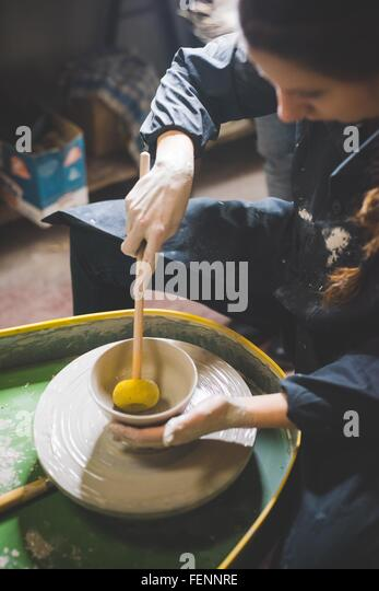 Young woman sitting at pottery wheel forming clay pot with diddler - Stock Image