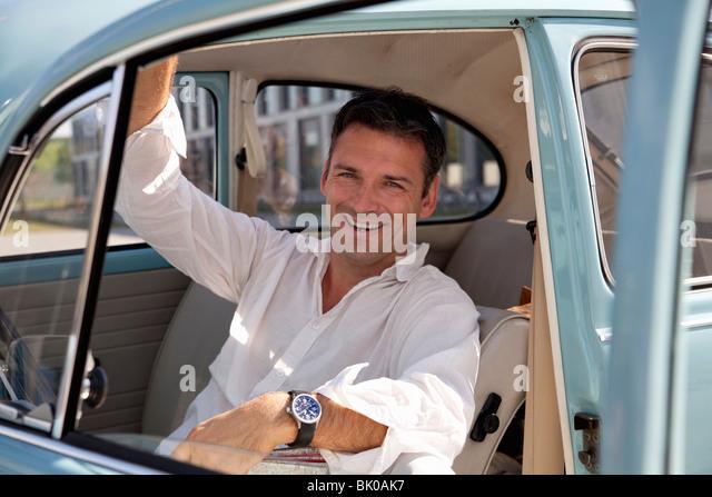 Man looking through car window - Stock Image