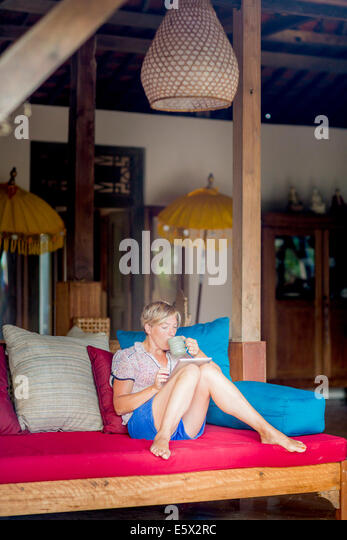 Woman relaxing with coffee and digital tablet in holiday apartment sitting room, Ubud, Bali, Indonesia - Stock-Bilder