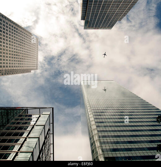 Plane flying past skyscrapers, Canada Square, London, England, UK - Stock-Bilder