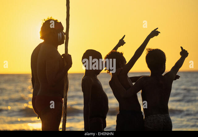 Aboriginal with a pole and children pointing at the sky at sunset, Darwin, Australia - Stock-Bilder